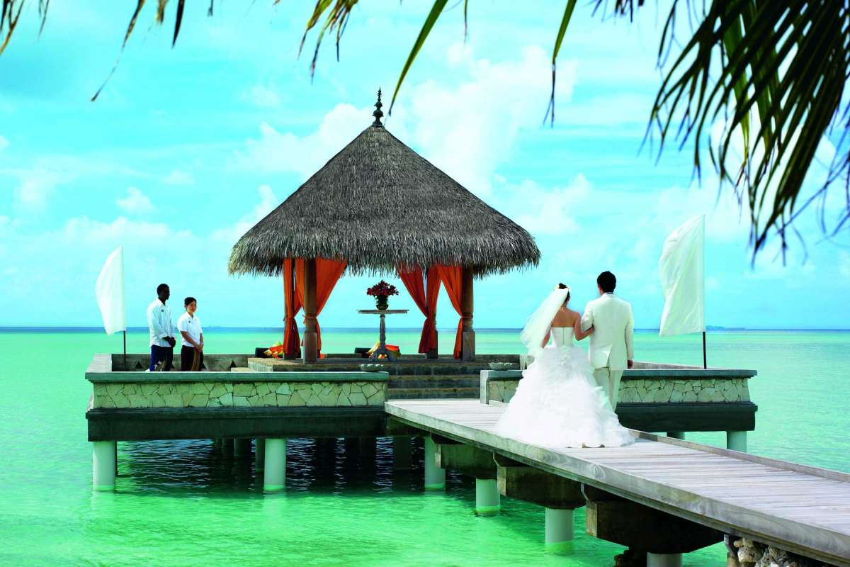 A bridal couple walks along a footbridge to a small wedding pavilion built on the water