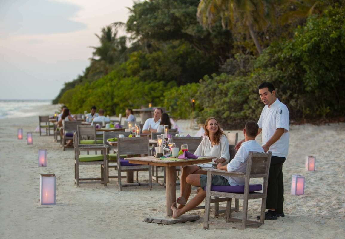 View on the guests sitting directly at the beach at the tables of By The Beach Restaurant at Soneva Fushi
