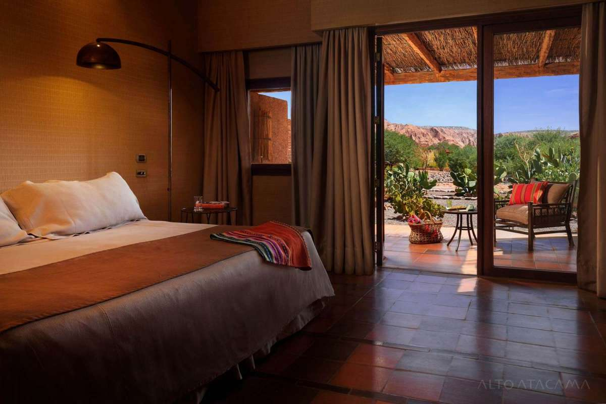 View on the bed of one of the Quitor-Rooms at Alto Atacama with an open terrace-door