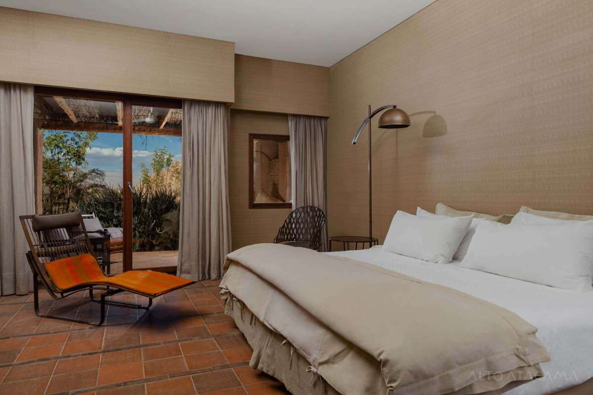 View of the bed, a relax-chair and the terrace in one of the Catarpe Rooms at Alto Atacama