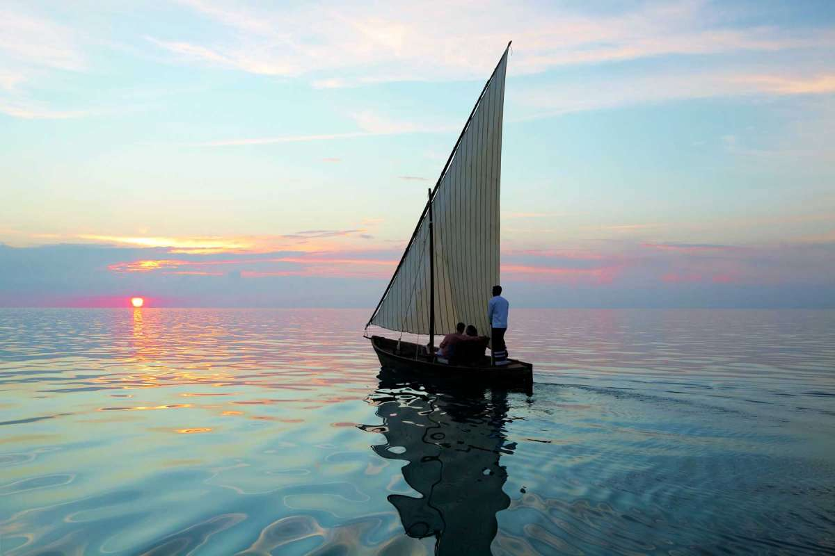 A couple sailing on a small sailboat towards the sunset